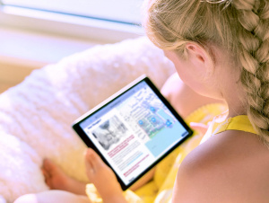 Child holding a tablet device reading through a digital consultation.